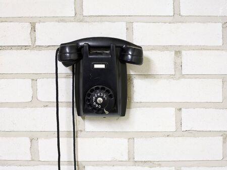bakelite: Black bakelite telephone on a brick wall.