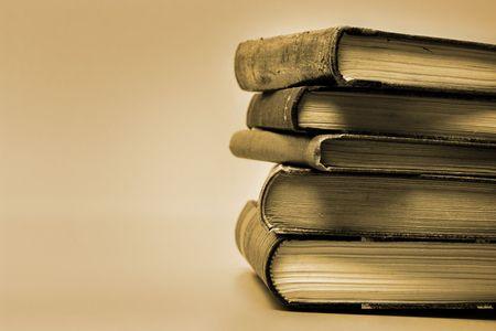 antics: Sepia toned image of stacked books.