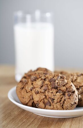 Chocolate chip cookies on a plate and a glass of milk in the background photo