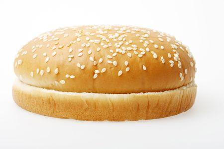 burger on bun: A hamburger bun on a light grey surface.