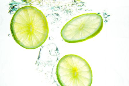 Fresh Lime splashing into water.