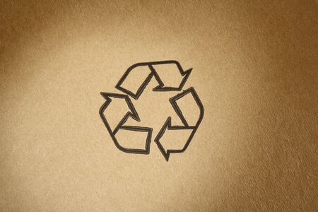 Recyclable universal symbol, printed on brown cardboard photo
