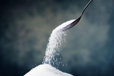 Adding sugar with a spoon.