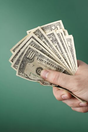 A Hand holding a small bunch of old wrinkled US Dollars photo