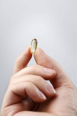 Fingers holding an Omega 3 fish oil capsule Stock Photo - 3436017