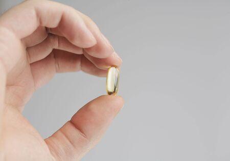 Fingers holding an Omega 3 fish oil capsule photo
