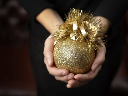 Female hands holding a gold colored christmas ball ornament Stock Photo - 3638792