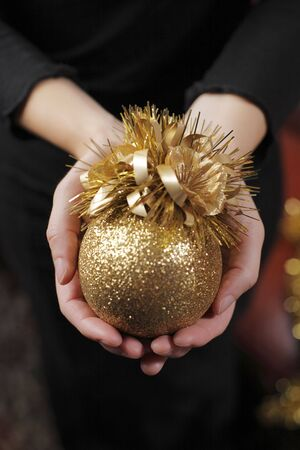 Hands of a woman holding a christmas ball ornament Stock Photo - 3638799