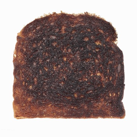 burnt toast: Isolated slice of burned toast Stock Photo