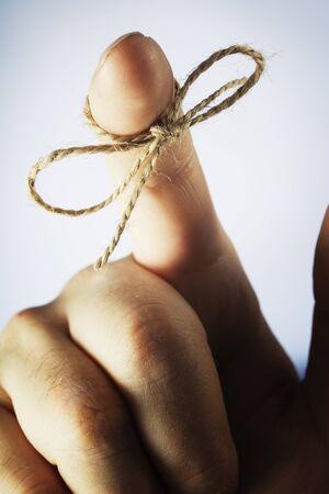 A piece of string tied around index finger photo