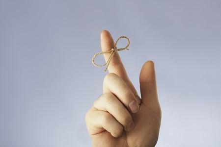 Una cuerda atada alrededor de un dedo índice