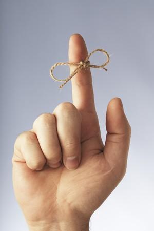atados: Un pedazo de hilo atado alrededor del dedo �ndice Foto de archivo