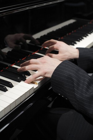 Hands of pianist playing on keys