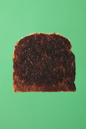 burnt toast: A Slice of burnt toast bread on green