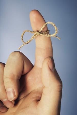 acordarse: Un trozo de cuerda atada alrededor del dedo �ndice Foto de archivo
