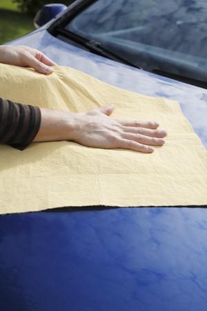 autolavaggio: Asciugando le mani una macchina blu con pelle di camoscio sintetico