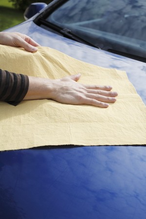 synthetic: Hands drying a blue car with synthetic chamois leather