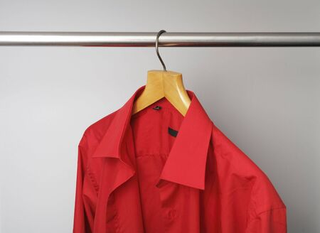 Red mens dress shirt hanging from a hanger Stock Photo