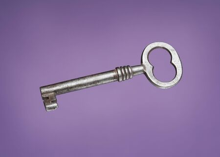 Old metallic key on lila background Stock Photo - 4766710