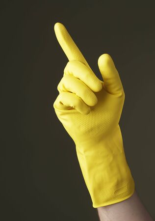 A Hand with yellow protective glove pointing with a finger Stock Photo - 4766730