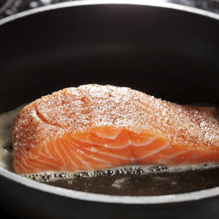 A Salmon fillet on a frying pan photo
