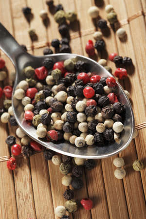 A mix of black, green, red and white peppercorns on a spoon photo