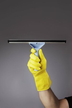 gloved: A gloved hand holding a squeegee