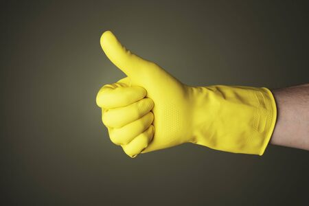 rubber gloves: A hand wearing a yellow protective rubber glove does thumb up gesture