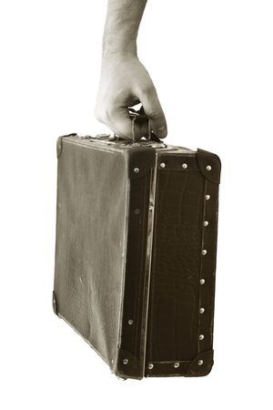 Sepia toned photograph of a hand holding an old suitcase. Short depth-of-field, the sharpness is in the hand. Stock Photo - 5091299