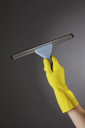 Hand with a yellow protective glove holding a rubber blade squeegee