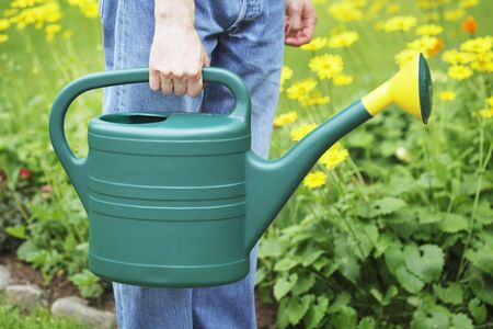 A Man holding a green plastic watering can in his hand. Stock Photo - 5108396