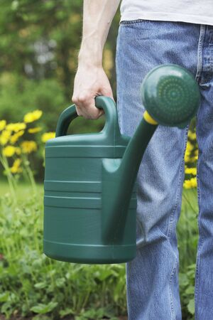 A Man holding a green plastic watering can in his hand. Short depth of field, sharpness is in the hand. Stock Photo - 5091285
