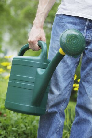 A Man holding a green plastic watering can in his hand. Short depth of field, sharpness is in the hand. Stock Photo - 5091291