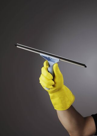 squeegee: Hand with yellow protective rubber glove holding a squeegee