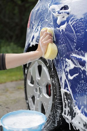 A Hand washing a blue car with a sponge Stock Photo - 5279798