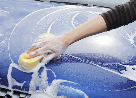 A Hand washing a blue car with a sponge photo