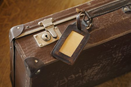 luggage tag: An old suitcase with a luggage tag.