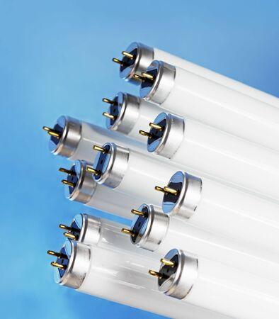 electrics: New fluorescent light tubes on blue background.