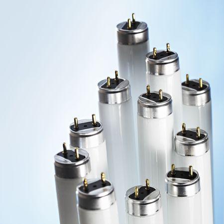 electrics: New fluorescent light tubes on blue Stock Photo