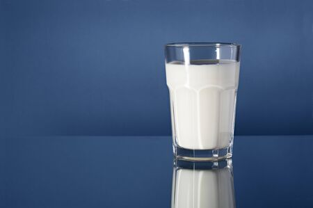 A Glass of milk on reflective blue background photo