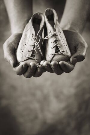 Dirty hands holding a pair of baby shoes. Very shallow depth of field. Stock Photo - 5777424