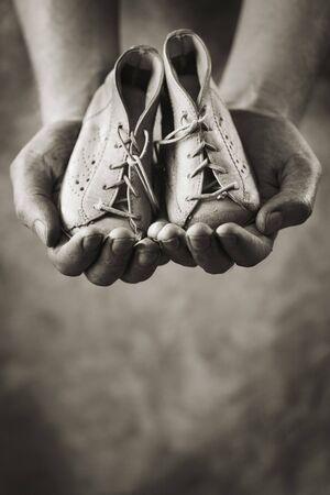 Manos sucias sosteniendo un par de zapatos de bebé. Muy poco profunda de la profundidad de campo. Foto de archivo