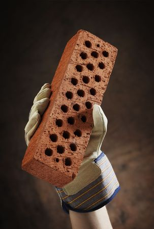 gloved: A gloved hand holding a perforated brick