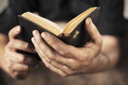 bible ouverte: Mains sales d�tenant une bible ancien. Profondeur de champ tr�s court