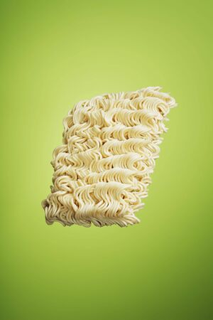 instant ramen: A block of dry instant ramen noodles on green background Stock Photo