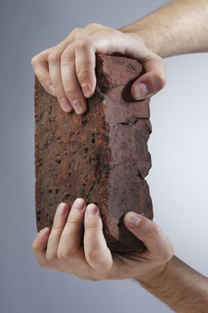 grip: Hands holding an old brick Stock Photo