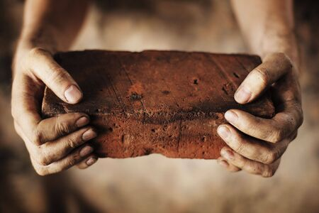 hand grip: Dirty hands holding an old brick Stock Photo