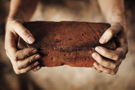 manos sucias: Manos sucias, sosteniendo un ladrillo viejo