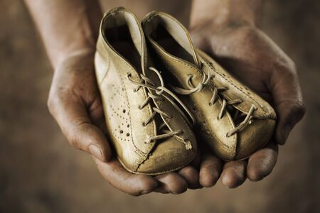 Dirty hands holding a pair of old childrens shoes. Stock Photo - 5777324