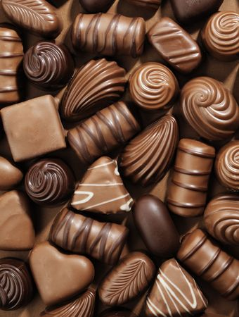 pralines: Assorted Chocolate pralines on brown background Stock Photo
